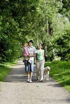Eine Familie mit Hund macht einen Spaziergang durch den Wald