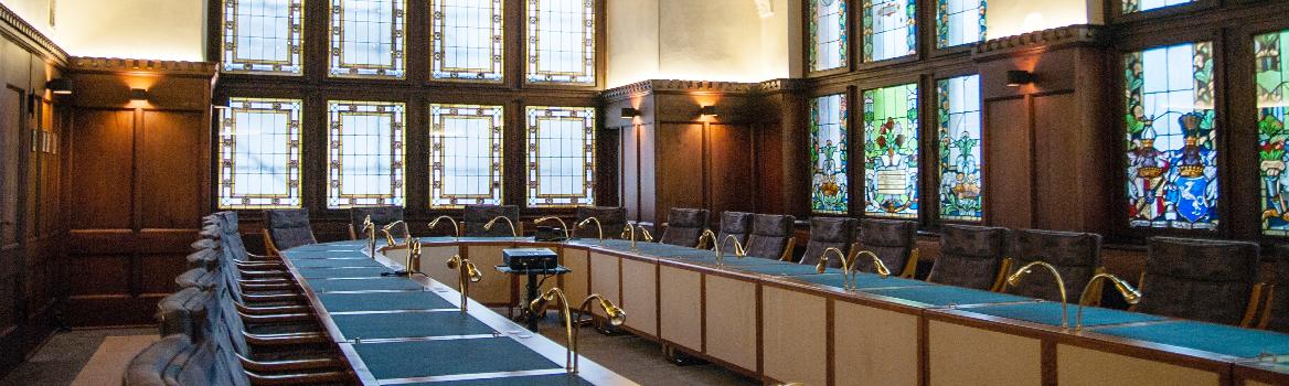 der historische Kreistagssaal mit holzvertäfelten Wänden und farbigem Fenstermosaik