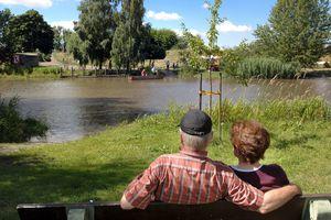 2 Senioren sitzen auf einer Bank in einem Park mit großem See.