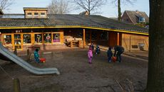 Bild vom Außenbereich einer KITA, spielende Kinder mit Betreuer/in